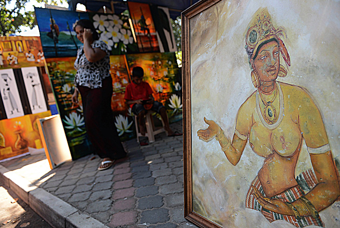 A Sri Lankan woman walks a painting at the annual painting exhibition known as 'Kala Pola' in Colombo  ? AFP Photo