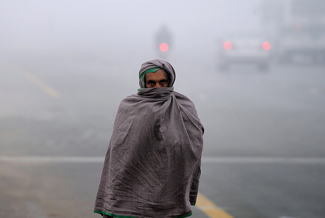A Pakistani resident covers his body with a warm shawl as he walks along a street during a cold and foggy morning in Islamabad on January 8, 2013. Ongoing foggy weather in Punjab and other parts of the country has badly affected flight and rail schedules. ? AFP Photo