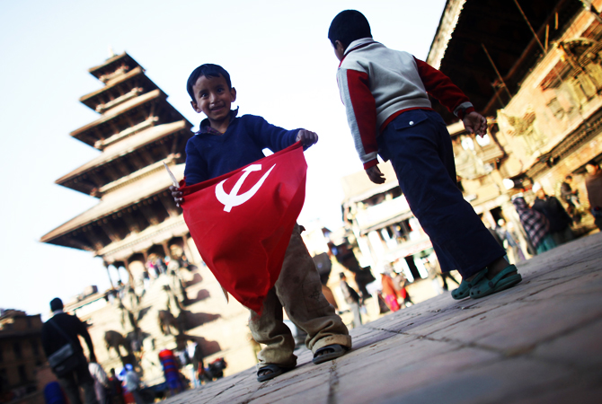 A Nepalese child plays with the flag of a communist party.
