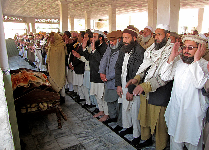 Local residents offer funeral prayers for a bomb blast victim in Mingora, the main town in the district, on January 11, 2013. An explosion at a religious gathering in Pakistan's northwestern Swat valley that killed 22 people and wounded more than 80 was caused by a bomb, officials said Friday. – Photo by AFP