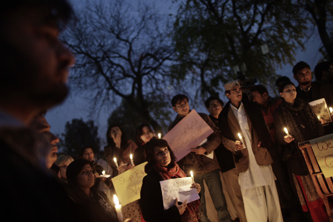 People hold banners and candles during a protest to condemn Thursday's deadly bombings in Quetta, in Islamabad, Pakistan, Friday, January 11, 2013. – Photo by AP