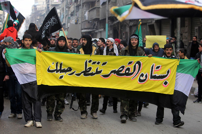 "Members of the Free Syrian Army hold a banner during a protest against Syria's President Bashar al-Assad in the Bustan al-Qasr district in Aleppo January 11, 2013. The banner reads: ""Bustan al-Qasr waits for your (Bashar al-Assad) leave."" – Photo by Reuters"