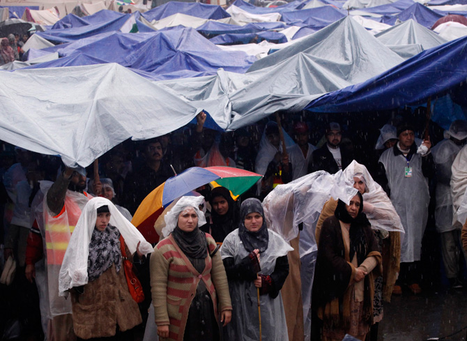 Supporters of Muhammad Tahirul Qadri, Sufi cleric and leader of Minhaj-ul-Quran, listen to him while standing in the rain during the fourth day of protest in Islamabad January 17, 2013. – Photo by AFP
