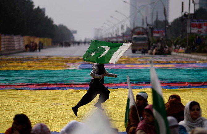 Supporters of  Tahir-ul-Qadri listen to speeches while waiting his arrival to Islamabad, as a youth runs across the street holding a national flag, in Islamabad, Pakistan, Monday, Jan. 14, 2013. ? Photo by AP