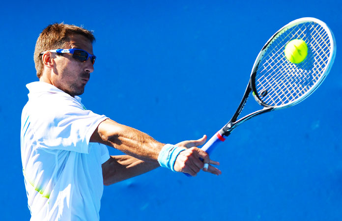 Spain's Tommy Robredo hits a return against Canada's Jesse Levine during their men's singles first round match.