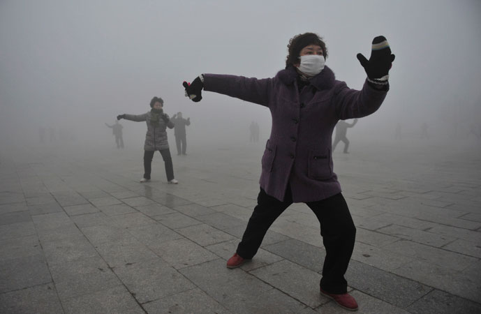 A woman wears a mask as she does her morning exercise outdoors in Fuyang, Anhui province. China's environmental watchdog ordered greater efforts to issue early warnings for air quality on Monday, as hazardous air pollution has hit many parts of the country in recent days, Xinhua News Agency reported. ?Photo by Reuters