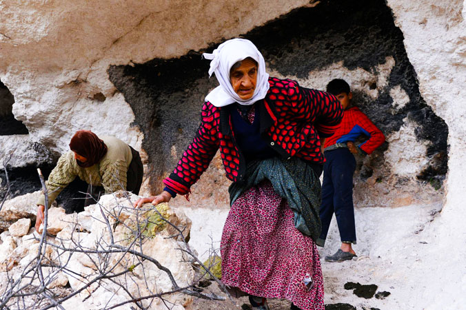 Syrian women who are also building a wall with rocks to protect the entrance of a cave that is now their home.