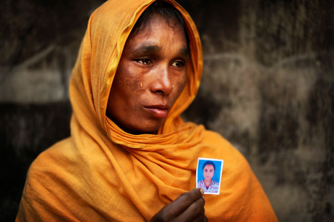Bangladeshi Zamiron Begum, weeps as she displays a photograph of her daughter Bobita Khatum, a senior sewing machine operator who died in the fire.