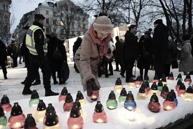 A woman lights a candle as she attends a memorial ceremony, at Raoul Wallenberg Square in Stockholm, Sweden. ?Photo by AFP
