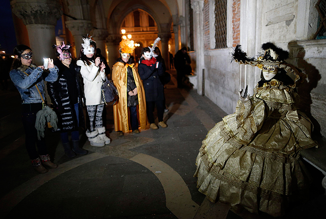 Nadia (R), wife of Marco Dilauro, poses at San Marco Square in Venice, during the Carnival. ? Reuters Photo