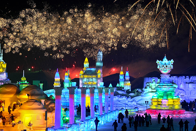 This picture taken on January 5, 2013 shows people visiting Ice and Snow World as fireworks fill the sky at the opening ceremony of the 2013 Harbin International Ice and Snow Festival in Harbin. ? AFP Photo