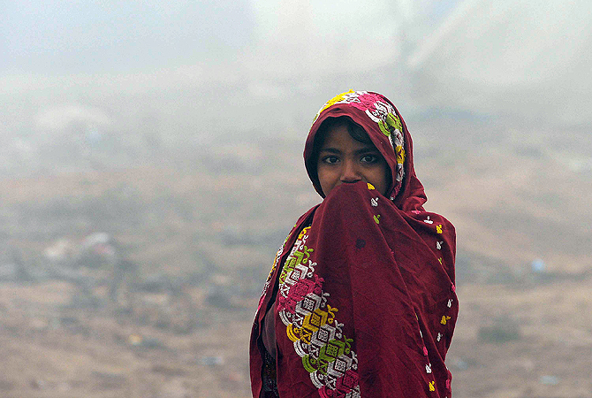 A Pakistani girl looks on during a cold and foggy day at a slum area of Peshawar on January 7, 2013.  Several major cities of Pakistan have been engulfed by thick fog causing traffic problems and flight cancellations. ? AFP Photo