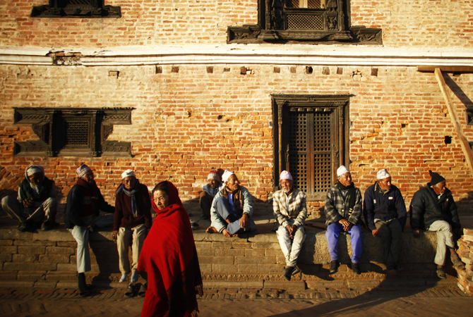 Nepalese elderly people sun bathe at Bhaktapur.