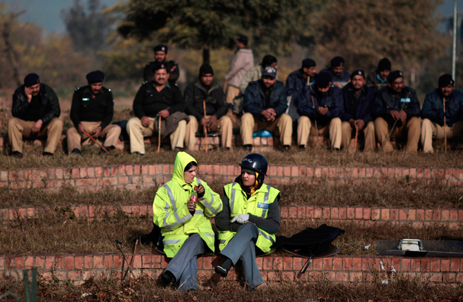 Two Pakistani police officers talk near the Parliament while resting in preparation for a march led by cleric Tahir-ul-Qadri, which is expected to arrive in Islamabad later in the day, in Islamabad, Pakistan, Monday, Jan. 14, 2013. ? Photo by AP