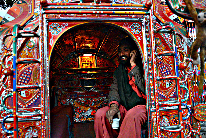 A passenger talks on his phone while travelling in a decorated minivan in Rawalpindi. — AFP Photo