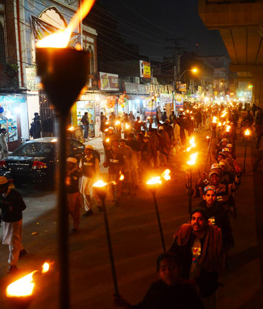 Pakistanis carry torches during a celebration in Lahore. ?Photo by AFP