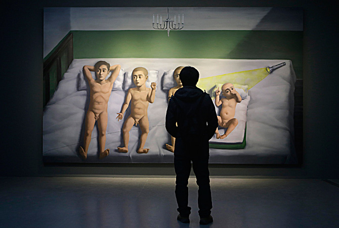 "A man looks at an oil painting titled 'Four Sons' by Chinese artist Zhang Xiaogang from his ""Amnesia and Memory Series"", during the Beijing Voice exhibition at Pace Beijing Gallery in Beijing's 798 art zone. ? Reuters Photo"