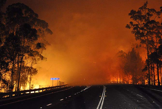 This handout picture taken late on January 8, 2013 and provided by New South Wales Rural Fire Service (NSW Rural Fire Service) on January 9, 2013 shows trees burning and smoke billowing from a fire along the Princes Highway at Deans Gap in the Shoalhaven area in New South Wales. A drop in temperatures helped firefighters battling blazes across Australia on January 9 but up to 30 wildfires were still raging out of control, destroying a handful of homes and forcing people to flee. ? AFP Photo