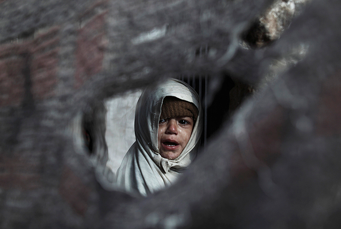 A girl cries while she stands behind a torn makeshift curtain at the entrance of her house in a slum on the outskirts of Islamabad January 8, 2013. ? Reuters Photo