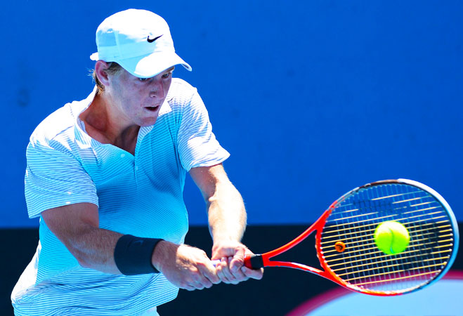 Australia's Luke Saville hits a return against Japan's Go Soeda during their men's singles first round match.