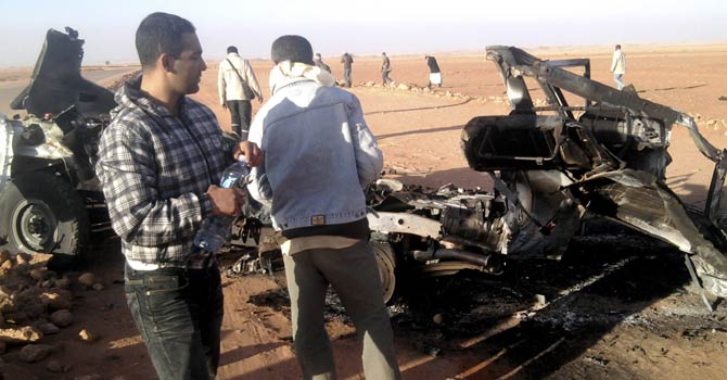 "In this undated photo, men look at the wreckage of a vehicle near Ain Amenas, Algeria. Algerian bomb squads scouring a gas plant where Islamist militants took dozens of foreign workers hostage found ""numerous"" new bodies on Sunday, Jan 20, 2013 as they searched for explosive traps left behind by the attackers, a security official said, a day after a bloody raid ended the four-day siege of the remote desert refinery.  - AP Photo"