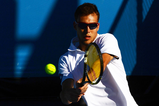 Poland's Jerzy Janowicz hits a return against Italy's Simone Bolelli during their men's singles first round match.