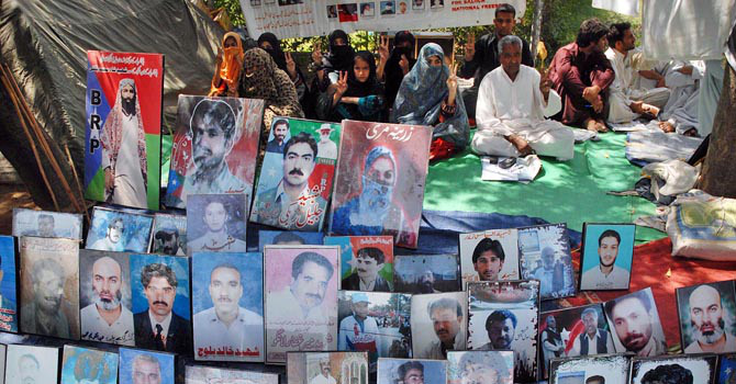 The file photo shows photographs of missing persons. - File Photo