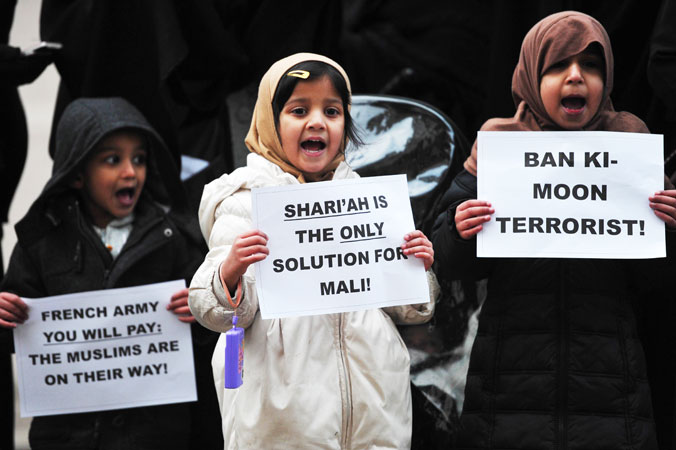 Children hold up signs as they join a protest in response to French military action in Mali outside the French embassy in central London. ?Photo by AFP