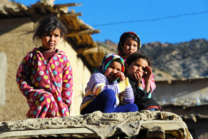 Moroccan children sit outside their homes in Anfgou in the High Atlas mountains. More than 20 tons of food and hundreds of duvets and mattresses were distributed to villagers who are facing an unusually bitter winter, causing hardship not usually associated with Morocco. ?Photo by AFP