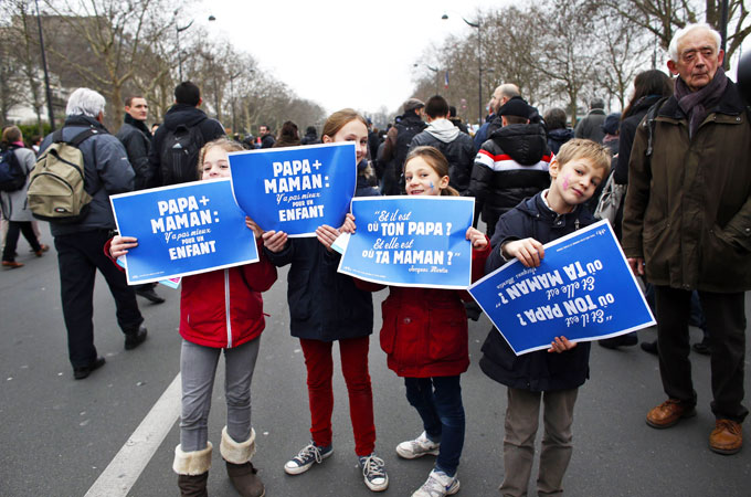 Children hold placards reading ?A father and a mother, nothing is better for a child? as they take part in a protest organized by the French far-right party, Front national (FN) party, against same-sex marriage in Paris. ?Photo by AFP
