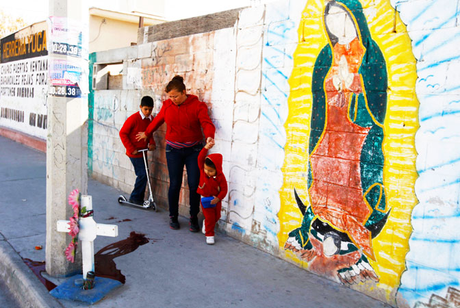 A woman walks with two children past a puddle of blood at a crime scene in Ciudad Juarez. ?Photo by Reuters