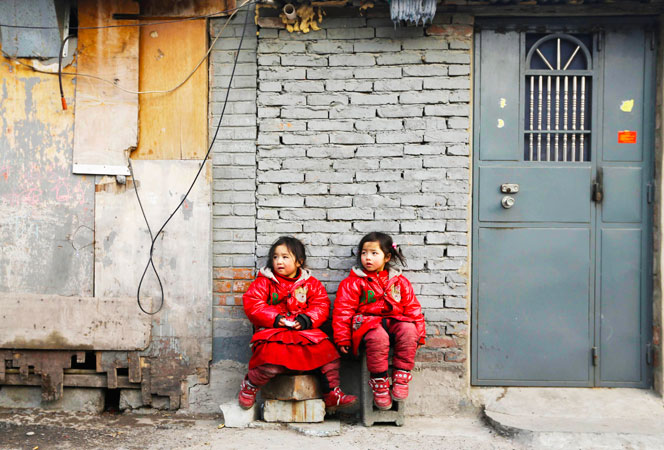 Two four-year-old twin sisters rest against a wall at a poor residential area for migrant workers on the outskirts of Beijing. Chinese rural children are expected to get better care from the government including more nutritious meals, safe school buses and better accommodation facilities. Currently, China has about 58 million rural children living away from their parents. ?Photo by Reuters