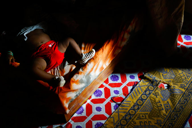 In this Nov 19, 2012 photo, eight-month-old Mohamed sleeps on the family bed as his father, Ibrahim, argues with the family of the boy's mother, Fatmata, after Ibrahim allegedly helped his new girlfriend beat up Fatmata, in Freetown, Sierra Leone. Domestic violence is a problem all over West Africa. ?Photo by AP