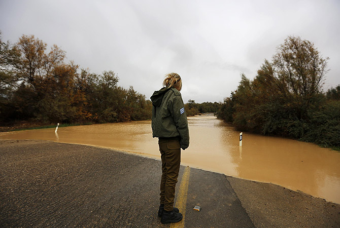 An Israeli soldier looks on a flooded road at the Negev desert near Kibbutz Zeelim.   At least 17 people have died due to a winter storm in Lebanon, Jordan, Turkey, Israel and the Palestinian territories. Meteorological agencies in Israel and Lebanon both called it the worst storm in 20 years.?Photo by Reuters