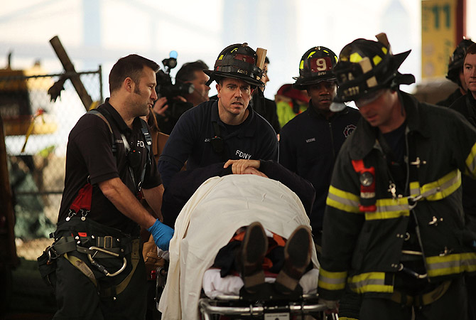 An injured person is carried to a waiting ambulance following an early morning ferry accident during rush hour in Lower Manhattan, in New York City. About 50 people were injured in the accident, which left a large gash on the front side of the Seastreak ferry at Pier 11.?Photo by AFP
