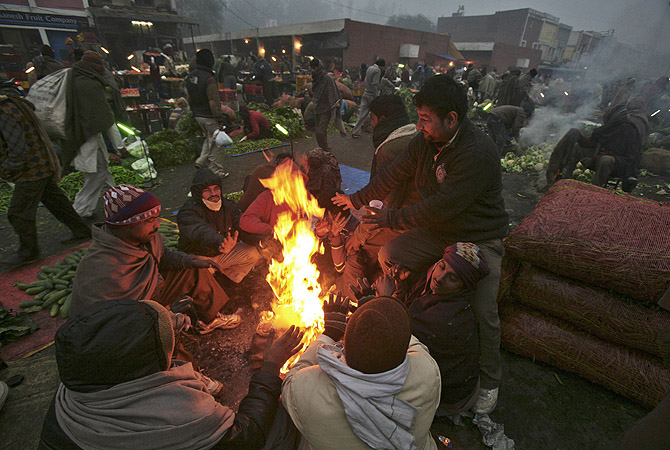 People warm themselves by a fire at a vegetable wholesale market on a cold winter morning in the northern Indian city of Chandigarh . The current cold weather in northern India has killed more than 100 homeless people, an aid group said last week. Temperatures in Chandigarh have dipped to 1.5 degrees Celsius, according to information posted on India's meteorological department website.—Photo by Reuters