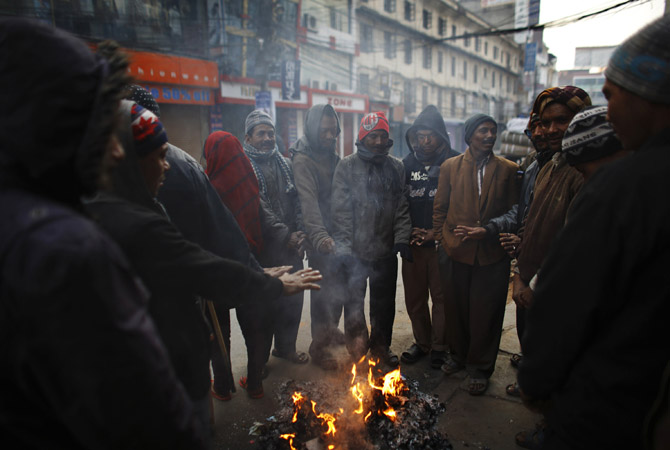 Nepalese people warm themselves by a fire during a cold winter morning in Kathmandu January 8, 2013. Nepal's Meteorological Forecasting Division (MFD) said capital Kathmandu experienced its coldest morning in three years with the temperature dropping to 0.7 degree Celsius (33 degrees Fahrenheit).   REUTERS/Navesh Chitrakar (NEPAL - Tags: SOCIETY ENVIRONMENT)