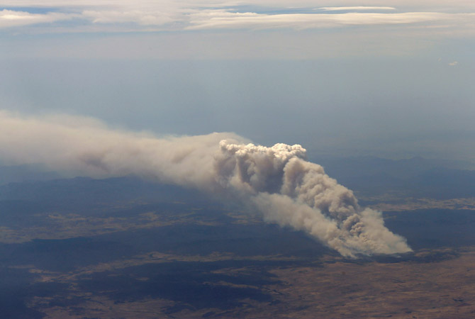 "Smoke rises from the Yarrabin bushfire, burning out of control near Cooma, about 100km (62 miles) south of Canberra. Severe fire conditions were forecast for Tuesday, replicating those of 2009, when ""Black Saturday"" wildfires in Victoria state killed 173 people and caused $4.4 billion worth of damage.—Photo by Reuters"