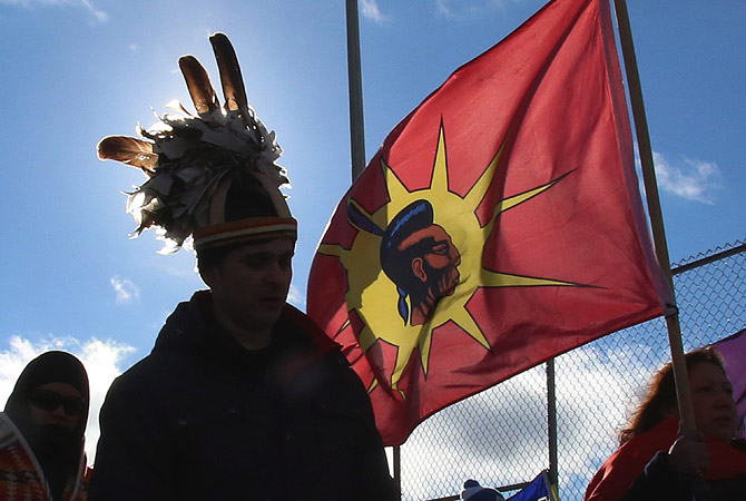 "First Nations ""Idle No More"" demonstrators march and block the International Bridge between the Canada and U.S. border near Cornwall, Ontario, Canada to protest proposed changes to environmental laws and land rights in Canada. —Photo by AP"