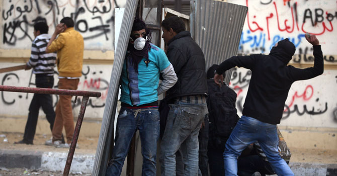 Egyptian protesters take cover as they clash with riot police, not seen, near Tahrir Square, Cairo, Egypt, Friday, Jan. 25, 2013. — Photo AP