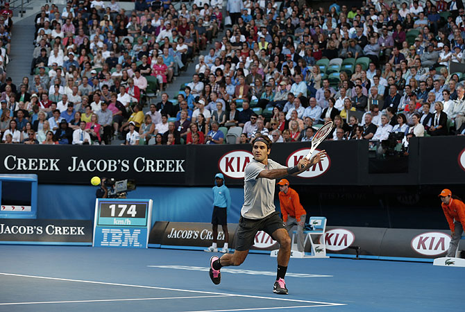 Switzerland's Roger Federer makes a backhand return to Australia's Bernard Tomic. -Photo by AP
