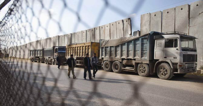 Palestinians walk past trucks loaded with gravel at the Kerem Shalom crossing between Israel and the southern Gaza Strip Dec 30, 2012. - Reuters