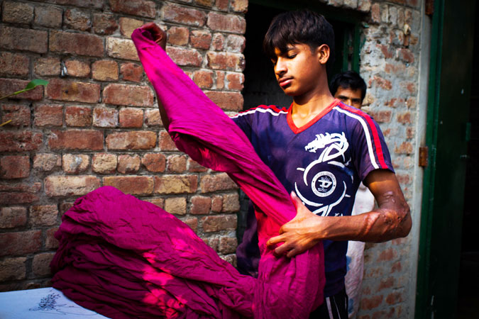 A factory worker dyes a set of shalwar pants magenta.