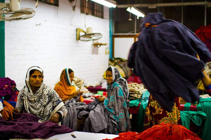 Inside the factory, women work to stitch elastic waistband into all of the shalwars.