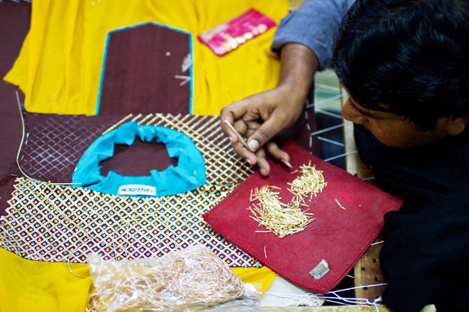 A factory worker hand stitches a gold lattice pattern onto a shirt.