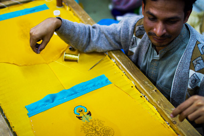 Another worker embroiders a turquoise design onto a suit.