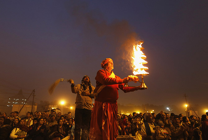 "A Hindu priest holds an oil lamp as he performs evening prayers near the banks of river Ganges ahead of the ""Kumbh Mela"" (Pitcher Festival) in the northern Indian city of Allahabad.?Photo by Reuters"