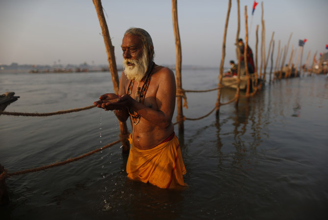"A devotee prays before taking a dip in the waters of the holy Ganges river ahead of the ""Kumbh Mela"" (Pitcher Festival) in the northern Indian city of Allahabad.?Photo by Reuters"