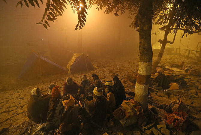 Indian holy men sit around a bonfire amidst morning fog after arriving at Sangam, the confluence of the rivers Ganges, Yamuna and mythical Saraswati, ahead of the Maha Kumbh festival in Allahabad, India.?Photo by AP
