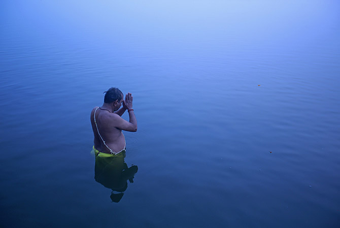 A Hindu devotee stands in the waters of river Ganges to offer prayers to Sun god at dawn in Varanasi, in the northern Indian state of Uttar Pradesh.?Photo by Reuters